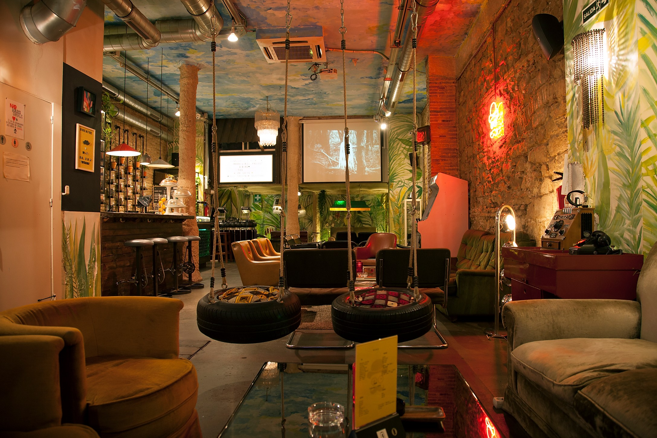 soft chairs and a large screen for watching football in Raval club