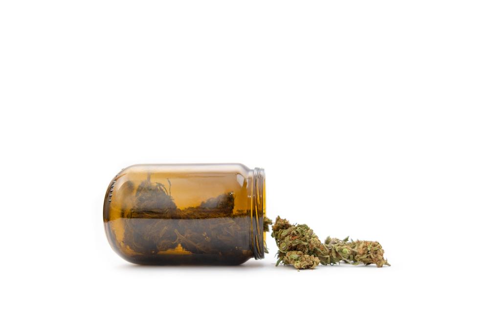 glass bottle with marijuana buds